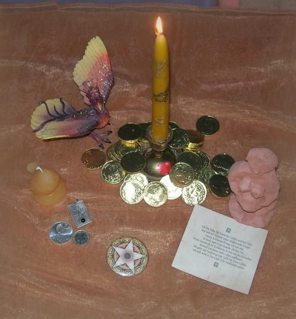 Von links nach rechts: Der Phönix, meine persönliche Beziehung zur Sternschnuppe, eine kleine Vogelkerze, symbolisch für die Zaunköniginnen, eine 10 € Münze, mit einem astronomischen Motiv - ein Geschenk an mich von einer Hexenschwester, eine maltesische 1 € Münze mit  Göttinnenidol, ein Button, der die Münzen des Tarot repräsentiert, die Geldkerze mit einer Sternschnuppe in der Mitte, umgeben von Goldmünzen, die mir Frau Holle einst für gute Dienste schenkte, eine Runenkarte 'Fehu' und eine handgefertigte Göttin, die ich bei einem Julfest von einer Mithexe geschenkt bekam.